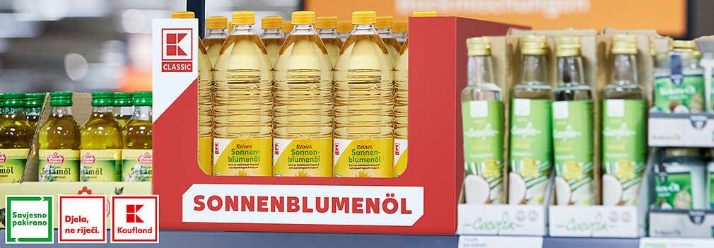 """Regal mit einem Karton voller K-Classic Sonnenblumenöl-Flaschen, die das """"Bewusster verpackt""""-Logo tragen"""