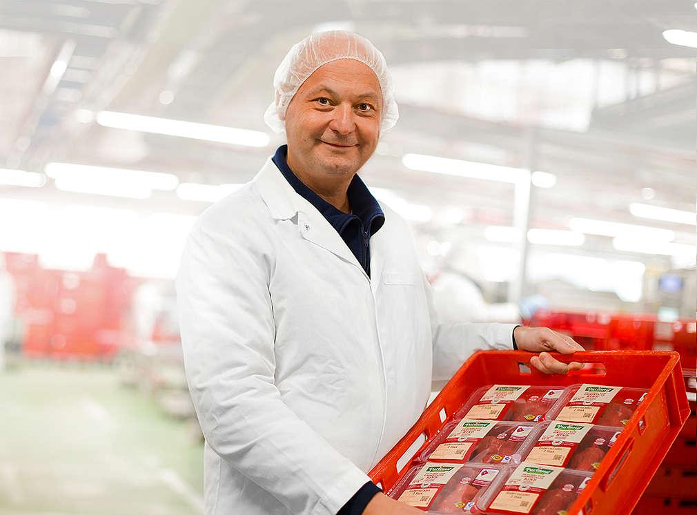 Metzger im Fleischwerk hält Kiste mit frischen Fleischprodukten